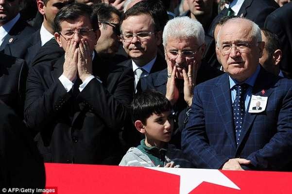 le Premier ministre turc Ahmet Davutoglu ( à gauche), le fils de Mehmet Selim procureur tué Kiraz et le président de l'Assemblée nationale turque Cemil Cicek (à droite) paré du cercueil