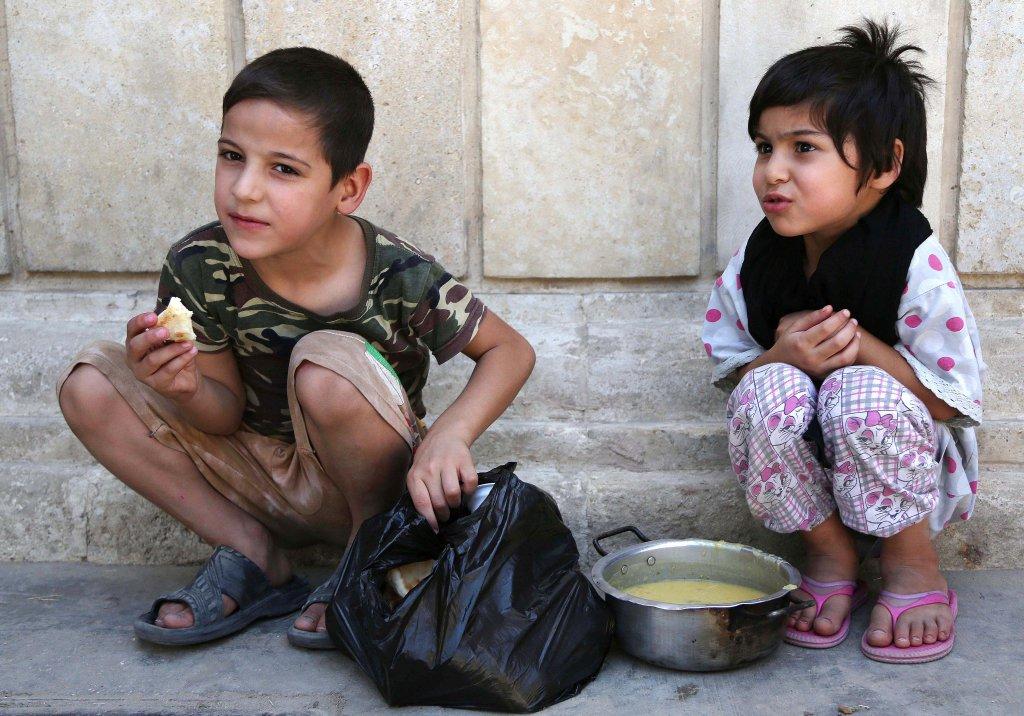 Les enfants mangent gratuitement de la nourriture distribué pour l'iftar, à la mosquée Abdul Khader al-Kilani à Bagdad, en Irak, le 23 Juin, 2015. (AP Photo / Karim Kadim)